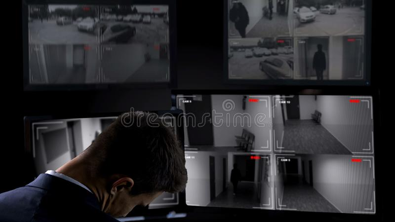 Security guard sleeping in front of surveillance camera, twenty-for-hour work. Stock photo stock images