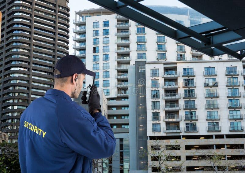 Security guard speaking with walkie-talkie. City. Digital composite of security guard speaking with walkie-talkie. City stock photo