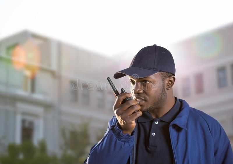 security guard speaking with the walkie-talkie in front of a building stock images