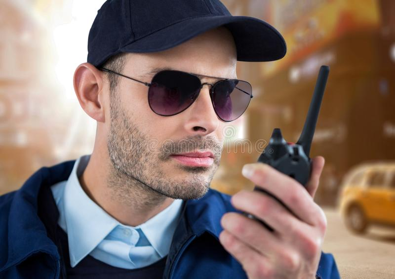 Security guard speaking with the walkie-talkie in the street. Digital composite of security guard speaking with the walkie-talkie in the street royalty free stock photos