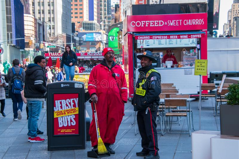 Security guard and street sweeper seen in Times Square Manhattan New York City in front of a small street cafe bar royalty free stock image