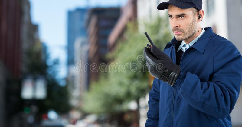 Security guard with walkie talkie against blurry street. Digital composite of Security guard with walkie talkie against blurry street stock images