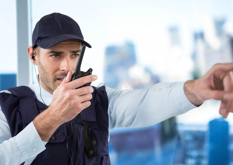 Security guard with walkie talkie pointing against blurry window showing city. Digital composite of Security guard with walkie talkie pointing against blurry stock image