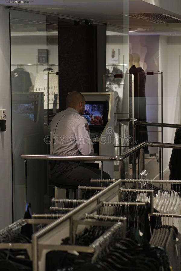 Security guard watching a store clothing from the screen. Mallorca, Spain- October 23,2015 Security guard watching a store clothing from the screen during Black stock photos