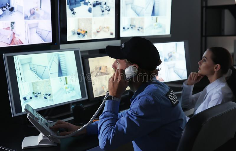 Security guards monitoring modern CCTV cameras in surveillance room royalty free stock photography
