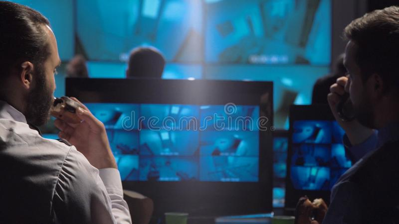Security guards watching the surveillance cameras. Security guards eating donuts while watching the surveillance cameras on screen while working late at night in royalty free stock photos