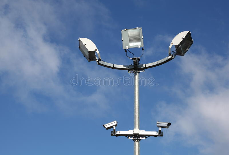 Security Lights Surveillance Cameras. A pole surmounted by three security lights and two surveillance cameras stands against a blue cloudy sky horizontal stock photo