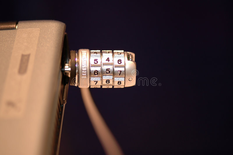 Security Lock for Laptop. A closeup view of a combination lock used to secure a laptop from being stolen while in a public area royalty free stock image