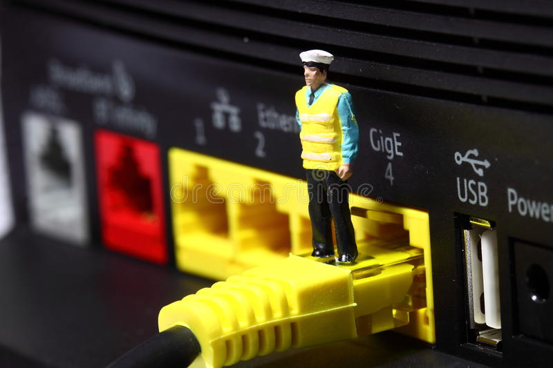 Security man router C. Miniature model security man standing on broadband router connector stock images