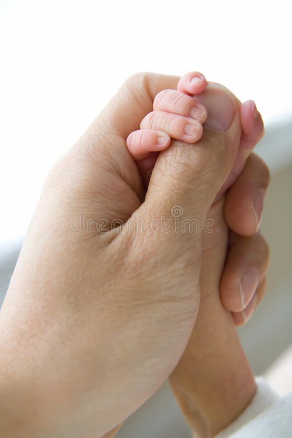 Security of a Parent. New born baby hand holding dad's thumb