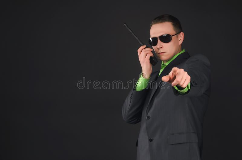 Security. Security agent is talking on the portable radio station and is showing ahead by his index finger isolated on black background. Face control. Suspicion stock image