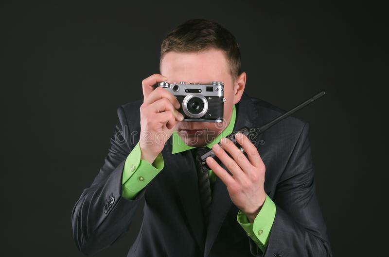 Security. Spy secret service agent with photo camera is photographing a compromising evidence and is talking on a portable radio station isolated on the black stock image