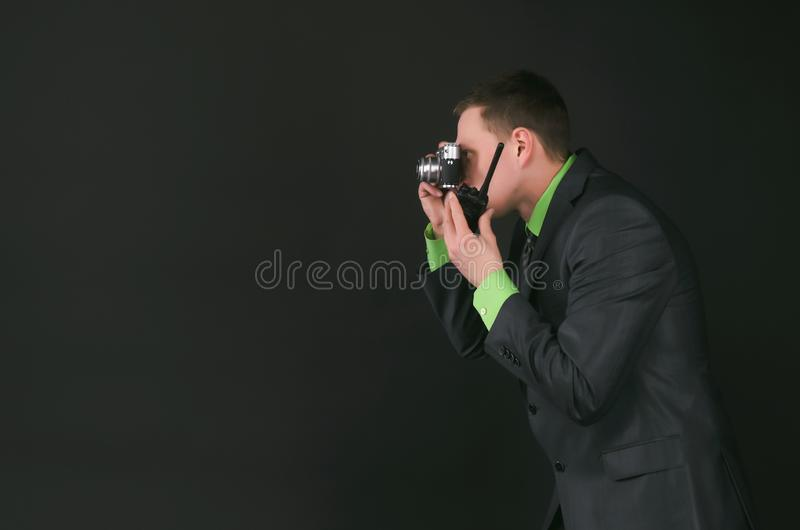Security. Spy secret service agent with photo camera is photographing a compromising evidence and is talking on a portable radio station isolated on the black stock photos