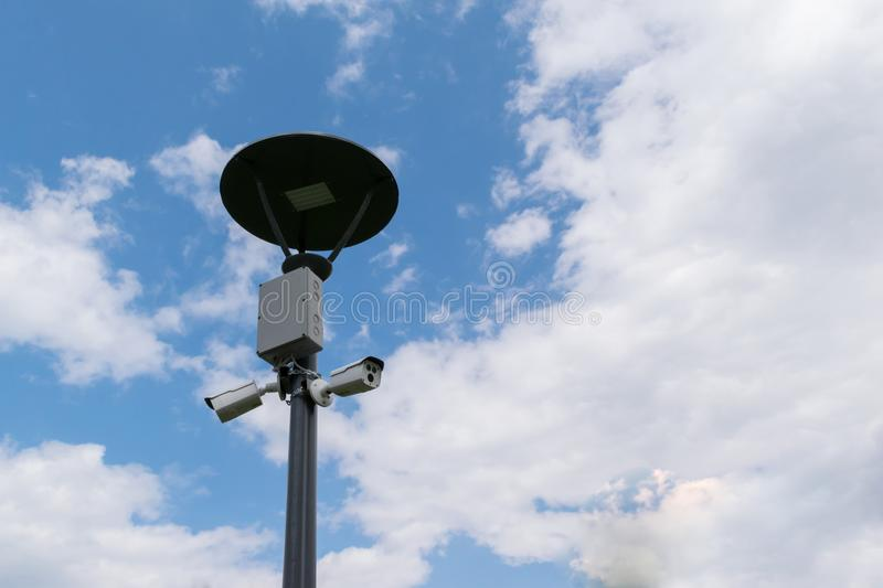 Security surveillance cameras mounted on street light pole with copy space royalty free stock images