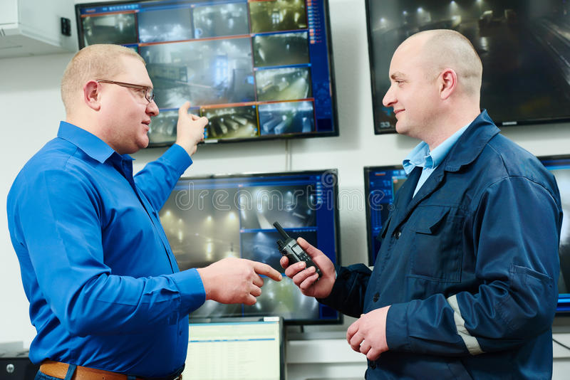 Security video surveillance. Security executive chief discussing activity with worker in front of video monitoring surveillance security system royalty free stock photography