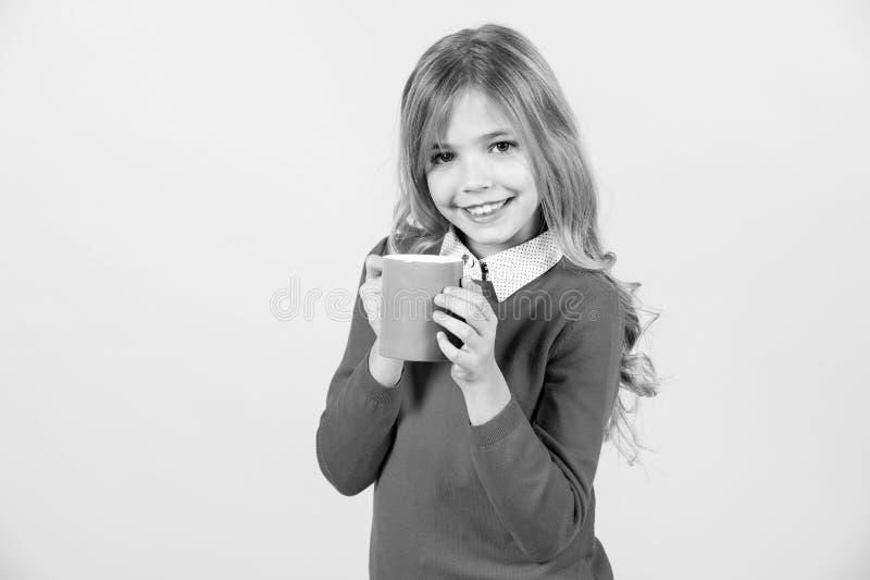 Sed, concepto de la deshidratación Sonrisa del niño con la taza azul en fondo anaranjado Muchacha con el pelo rubio largo en suét fotos de archivo