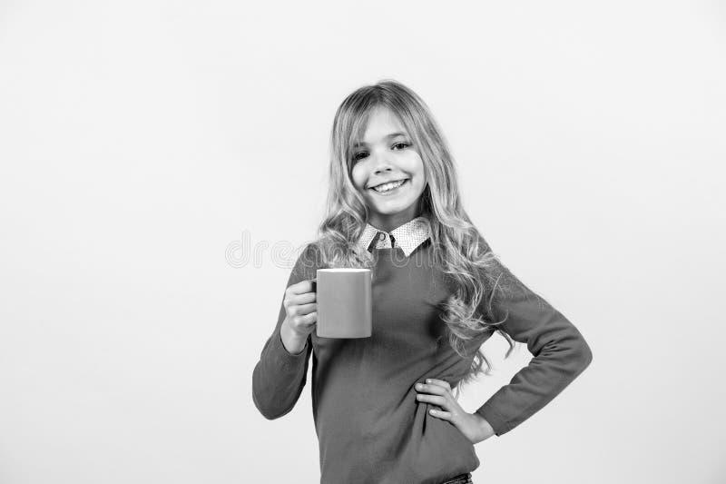 Sed, concepto de la deshidratación Sonrisa del niño con la taza azul en fondo anaranjado Muchacha con el pelo rubio largo en suét imagen de archivo