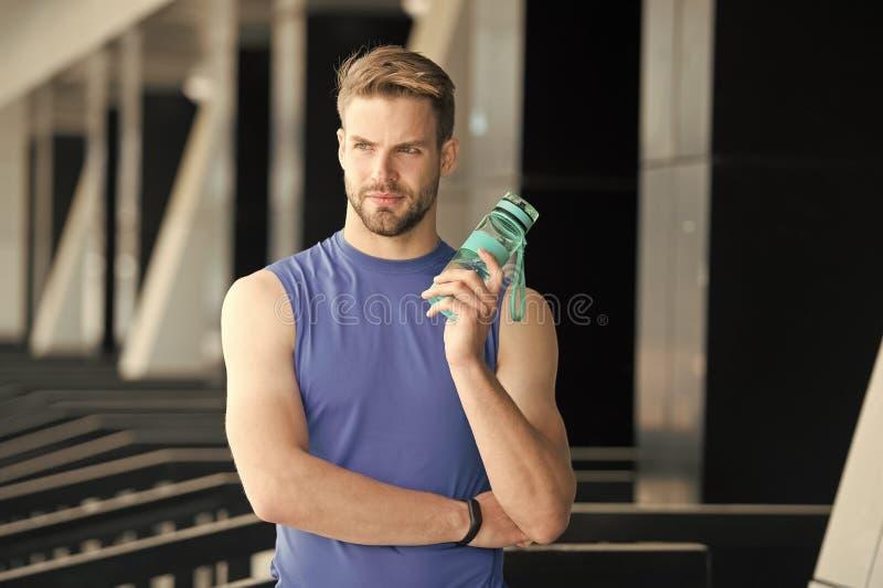 Sed y salud Botella de agua del control del deportista en estadio Hombre apto con el frasco plástico al aire libre Estancia hidra fotografía de archivo libre de regalías