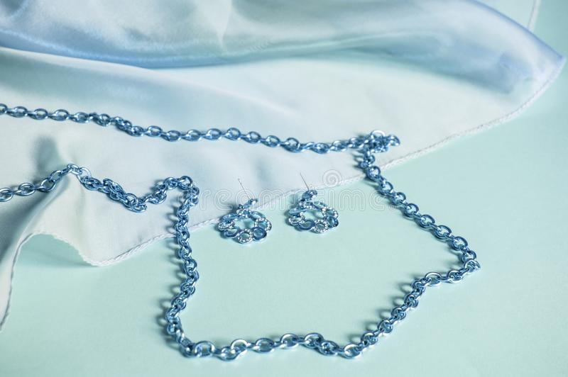 Seda azul, ondas cubiertas, cadena de plata y pendientes, imagen teñida en los accesorios azules, de lujo en colores pastel para  imagen de archivo libre de regalías