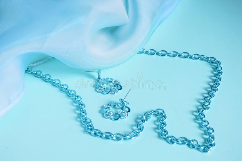 Seda azul, ondas cubiertas, cadena de plata y pendientes, imagen teñida en los accesorios azules, de lujo en colores pastel para  foto de archivo libre de regalías