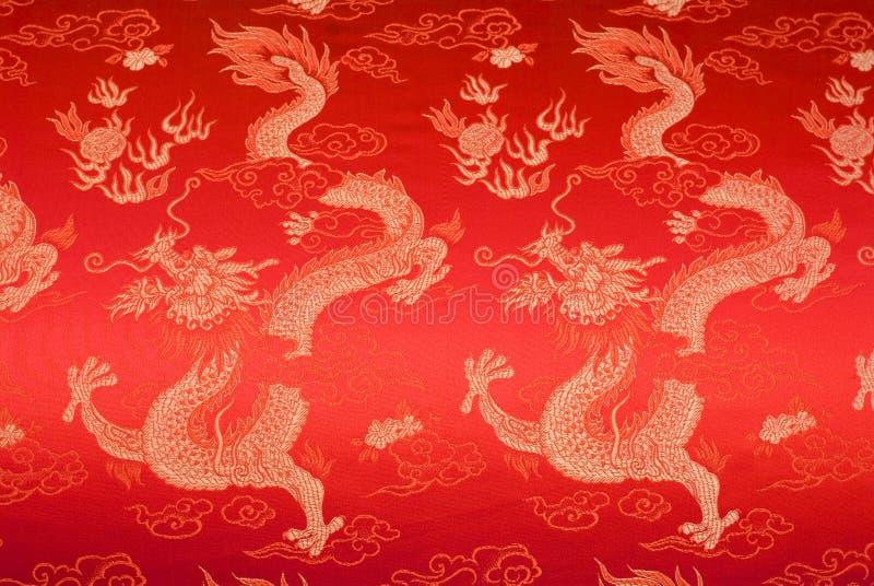 Seda china roja con los dragones y las flores de oro fotos de archivo