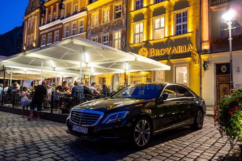 Sedan luxuoso da classe de Mercedes-Benz S estacionado na frente do restaurante do jardim de Brovaria em Poznan, Polônia fotos de stock