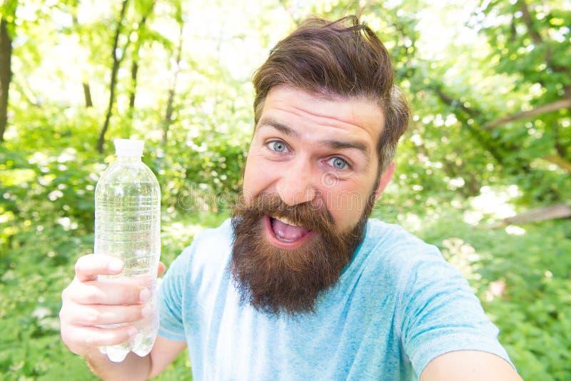 A sede é tudo Homem sedento Garrafa farpada da terra arrendada do homem da água potável para extinguir sua sede da sede ou imagens de stock