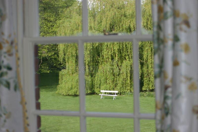 Sede di giardino veduta attraverso la finestra fotografie stock libere da diritti