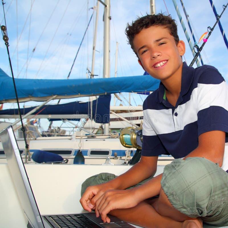Sede teenager del ragazzo sul computer portatile del porticciolo della barca fotografia stock