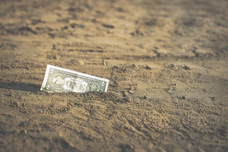 Sedel av värde av en dollar i sanden på stranden Begrepp av det billiga loppet och semestern royaltyfri bild