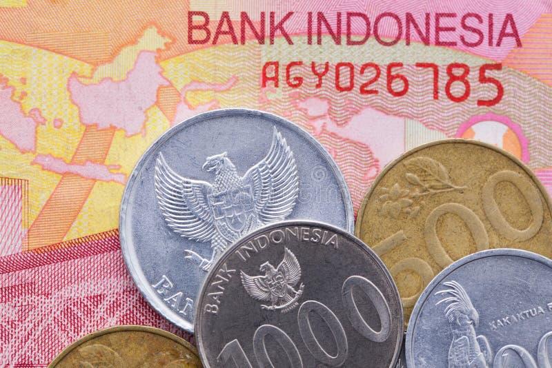 Sedel och mynt av rupiahen av Indonesien arkivfoto