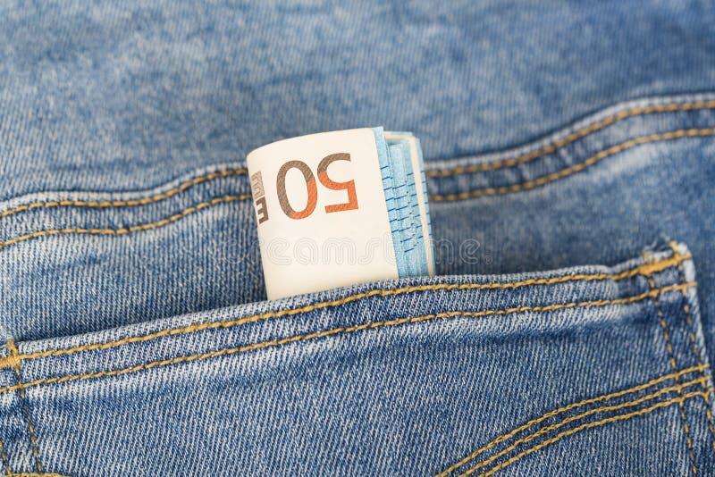 Sedelräkningar av eurovaluta som klibbar ut ur jeansen, stoppa i fickan royaltyfria foton