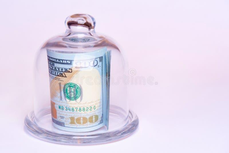 Sedelvärde hundra dollar under en exponeringsglaskupol på en vit bakgrund kopiera avstånd arkivfoto