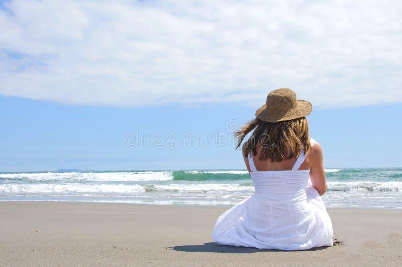 Sedendosi alla spiaggia fotografia stock libera da diritti