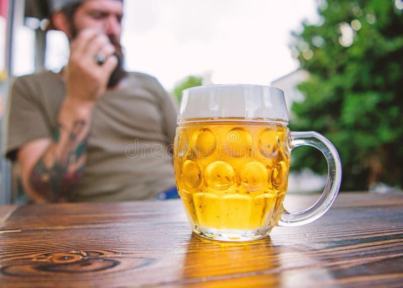 Sedendosi intorno alla birra bevente Birra bevente dei pantaloni a vita bassa nella barra Alcool bevente dell'uomo barbuto in pub fotografie stock libere da diritti