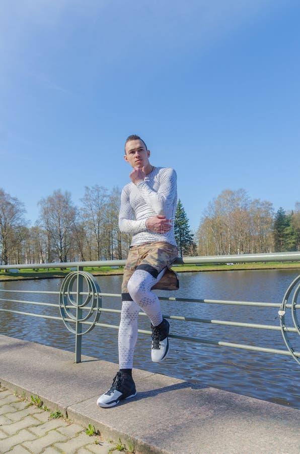 Sedendosi su un'inferriata dal fiume, uomo attraente nello sport bianco fotografie stock libere da diritti