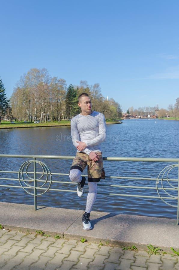 Sedendosi su un'inferriata dal fiume, uomo attraente nello sport bianco fotografia stock libera da diritti