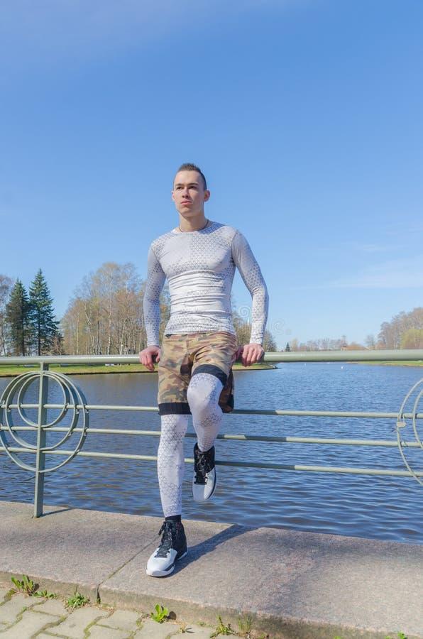 Sedendosi su un'inferriata dal fiume, uomo attraente nello sport bianco fotografia stock