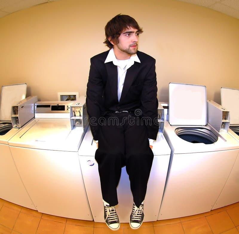 Sedendosi su una macchina della lavanderia fotografia stock