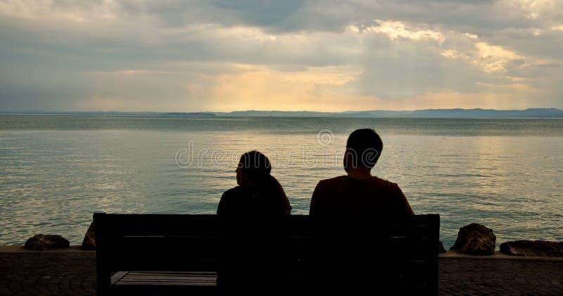 Sedendosi su una siluetta del banco fotografia stock