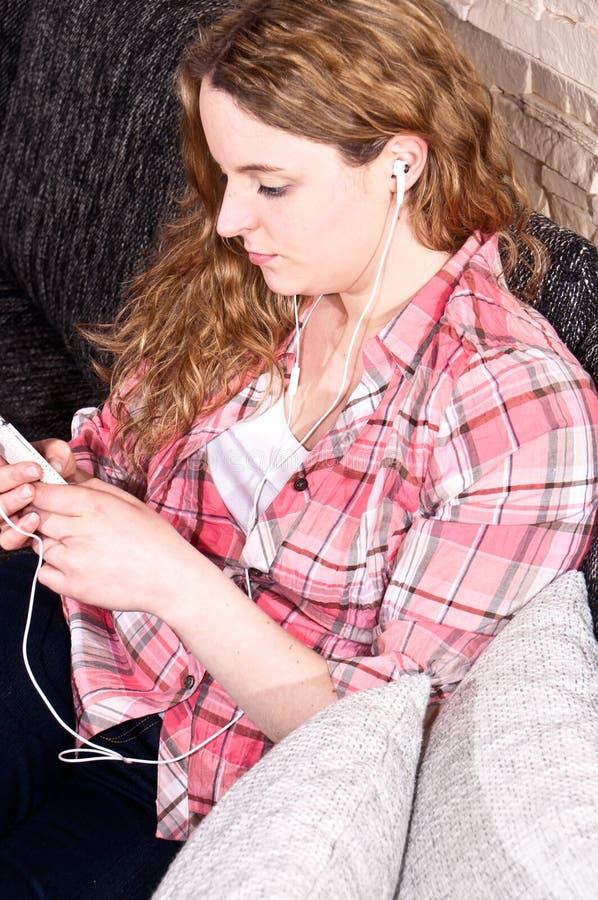 Sedendosi sullo strato mentre ascoltando la musica immagini stock libere da diritti