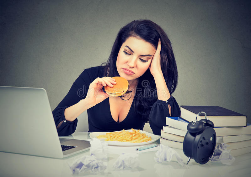 Sedentary lifestyle and junk food concept. Stressed woman sitting at desk eating hamburger. Sedentary lifestyle and junk food concept. Tired stressed woman stock image