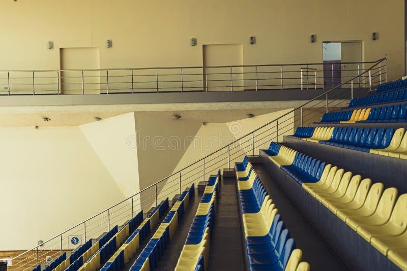 Sedi verdi dello stadio Sedili di plastica blu e gialli dello stadio dell'interno immagini stock