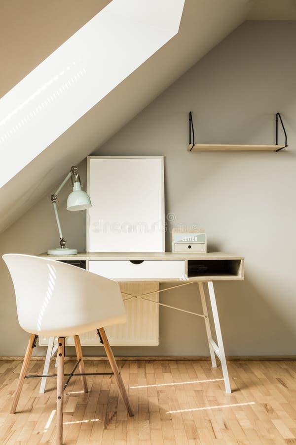 Sedia bianca allo scrittorio con la lampada ed il manifesto nell'area di lavoro luminosa int fotografie stock libere da diritti