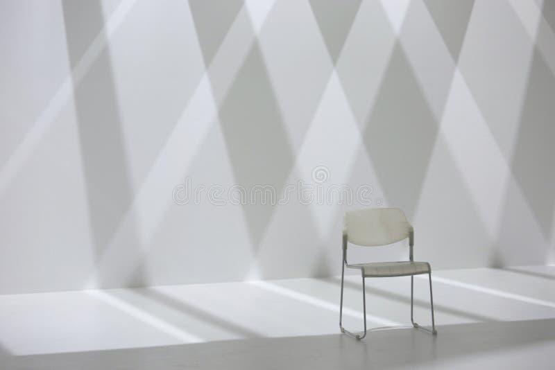 Sedia bianca davanti alla parete dell'ombra di forma del diamante immagine stock