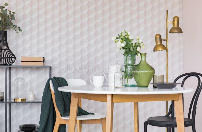 Sedia in bianco e nero alla tavola di legno nella sala da pranzo interna con i fiori e la lampada dell'oro Foto reale illustrazione di stock