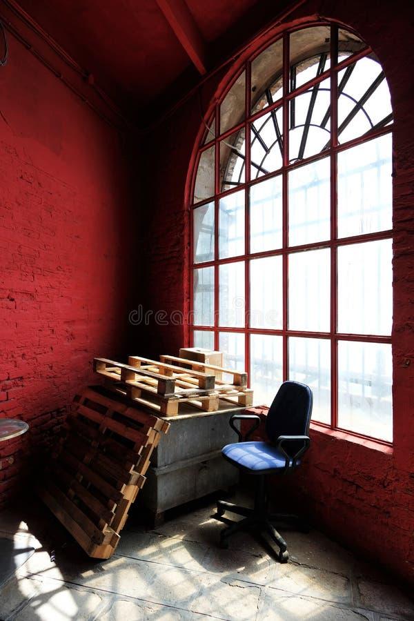 Sedia blu, pallet e parete rossa contro una grande finestra fotografia stock