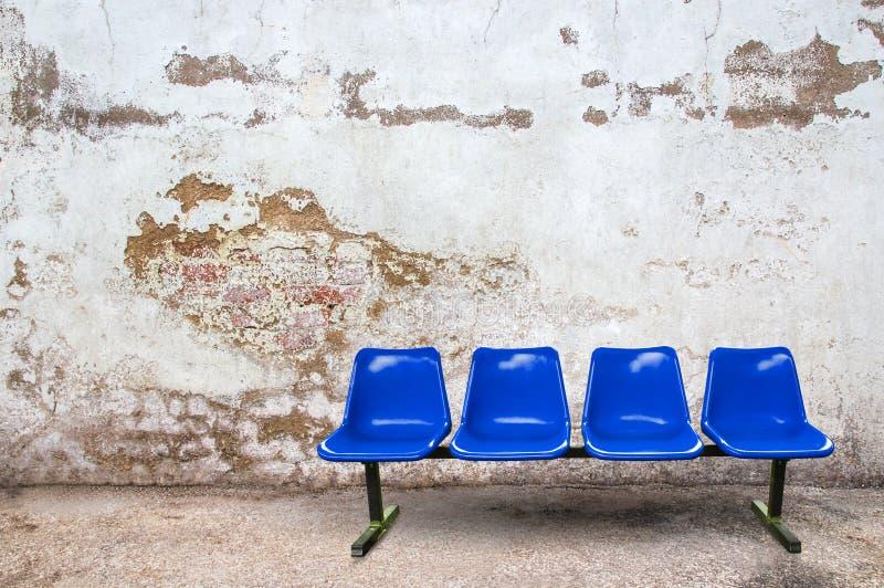 Sedia blu sul pavimento con il fondo di lerciume immagini stock