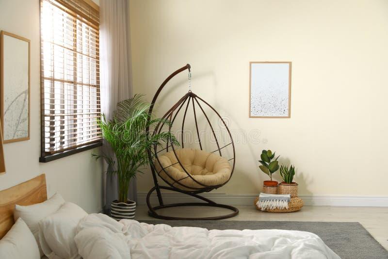 Sedia comoda dell'oscillazione con il cuscino in camera da letto immagine stock libera da diritti