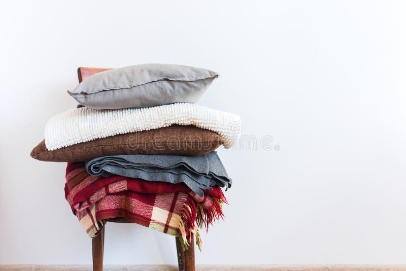Sedia d'annata con la parete di bianco del plaid della copertura del cuscino immagine stock